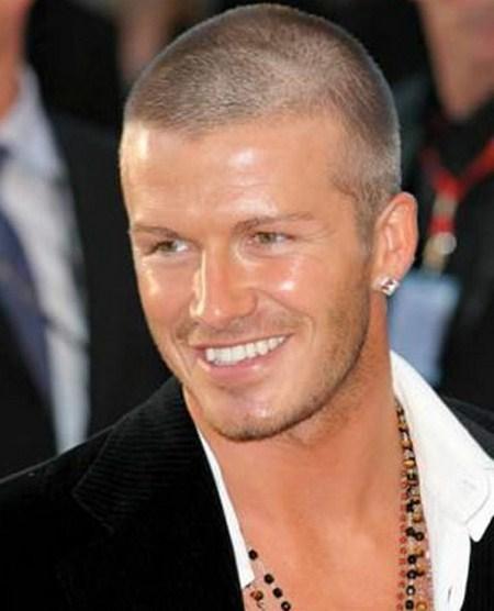 David Beckham posando y sonriendo. Tiene aros y un collar.